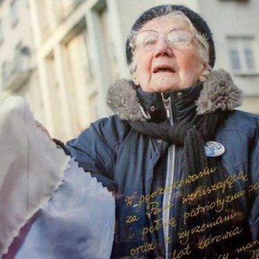 """Zdjęcie Starszej Pani z flagą z marszu KOD – """"My, Naród"""""""